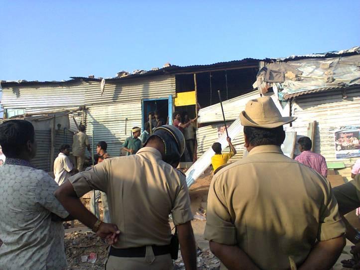 Goondas breaking EWS  homes while other goondas look on